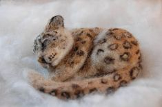 Known throughout the world for its beautiful fur and elusive behavior, the majestic snow leopard is found in the rugged mountains of Central Asia. This sleeping snow leopard is created from the softest corriedale and alpaca wool. The pose-able leopard is made using the needle felting