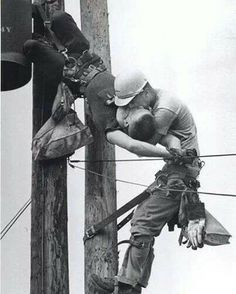 """""""Kiss of Life""""   This 1967 Pulitzer award-winning photo entitled """"Kiss of Life"""" shows a utility worker, J.D. Thompson, suspended on a utility pole and giving mouth to mouth resuscitation to a fellow lineman, Randall G. Champion, who was unconscious and hanging upside down after contacting a high voltage line. Champion survived and lived until 2002 (Jacksonville Florida)"""