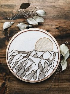 Inspired by the Sandia Mountains in New Mexico, this item was handmade using cotton thread and is stitched onto unbleached canvas. It is stretched on a 7-inch wooden embroidery hoop that is perfect for hanging right onto the wall. Each item is made to order.