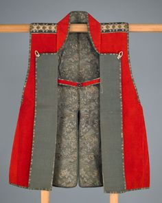 Warrior's surcoat (jinbaori)  19th century      Edo period     Brushed wool, silk brocade, silk with silver-leaf paper supplementary weft patterning, silk chirimen, silk cord, stencil-dyed leather, and gilded leather  H: 86.4 W: 69.9 cm   Japan