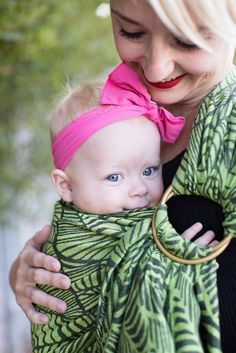 Key West Greenery - Cotton Ring Sling. An electric burst of color blends with an abstract design to give our Tula Ring Sling ultra hip appeal! 'Key West' Greenery has a large scale design reminiscent of palm leaves in a vibrant green and black color combination. This fresh display is woven in 100% cotton providing comfortable support while softening quickly with each wear. Tula Ring Slings come in sizes S/M and L/XL to provide you with a cozy fit for you and your baby.