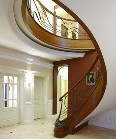 www.trabczynski.com ST455 Policzkowe schody gięte na wylewce betonowej wykonane z jesionu termowanego. Ręcznie kute stalowe balustrady z pochwytami drewnianymi. Słup wejściowy odlewany z brązu. Realizacja wykonana w prywatnej rezydencji , projekt – TRĄBCZYŃSKI / ST455 Curved concrete stair clad with thermo ash wood. Hand-wrought steel balustrades with wooden handrails. Entrance newel post cast of bronze. Private residential project, designed by TRABCZYNSKI.