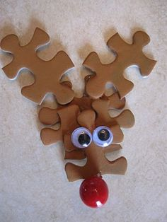 Old Puzzle Pieces      Arranged and Glued together in this manner:      Painted Brown      Add some Eyes      And a Nose      Some Ribbon on the back, and you've got yourself  A Very Puzzling Rudolph