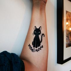 Black cat on laurels tattoo.