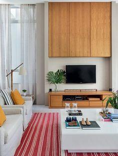 sala-de-tv-tapete-rack-freijo-painel-madeira-mesa-de-centro-laca-porta-velas (Foto: MCA Estúdio/Divulgação)