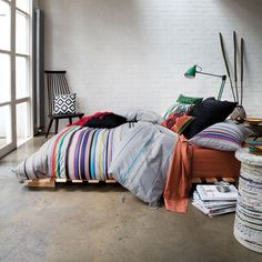 Shipping pallet bed frame + lots of different textiles #bedroom #layered_bed #concretefloor