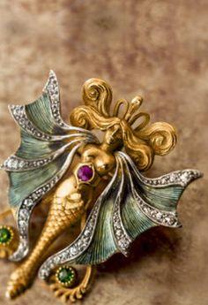 An art nouveau enamel, diamond and gem-set pendant brooch, circa 1905 designed as a winged water spirit mounted in platinum-topped fourteen karat gold; length: 1 3/4in.