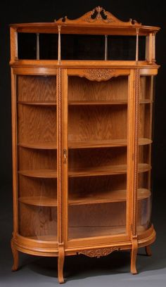 A VICTORIAN OAK CURVED GLASS CHINA CABINET WITH CARVED ROPE MOLD DECORATION AND TOP GALLERY SHELF WITH BEVELED GLASS MIRROR   C.1895