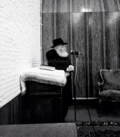 Leading Davening  (Prayer) Rebbe stands at his shtender podium, looking out.
