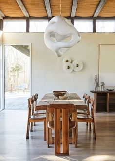 A biomorphic light sculpture by Rogan Gregory (sourced from R & Company) hangs above a reclaimed oak dining table flanked by 1970s Sapporo chairs. A plaster wall by Kamp Studios contributes to the textural contrast. Hamptons House, The Hamptons, Architecture Renovation, Stil Inspiration, Oak Dining Table, Dining Rooms, Dining Table Design, Dining Chairs, Nate Berkus