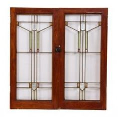 Matching set of original early 20th century craftsman or prairie style interior residential cabinet door windows. Simple geometric grid accentuated with art glass and clear beveled glass. Varnished white oak wood sash frames. Salvaged from a 1920 bungalow residence. Each window measures 33 1/2 x 16 inches.