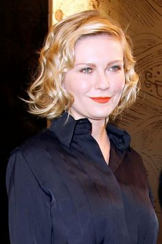 Actress Kirsten Dunst was sensational with her stunning, blonde hairstyle when she arrived for the Chanel show during Paris Haute Couture Fashion Week Spring/Summer 2011 at Pavillon Cambon Capucines. Completing her Chanel chic style, Kirsten Dunst got glam with her bouncy waves, deep side part and mid-length 'do.
