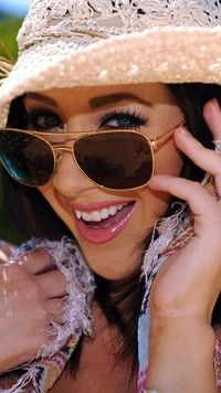 Uśmiechnięta Denise Milani w kapeluszu i okularach