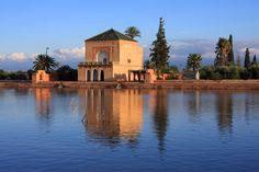 Morocco Marrakesh Menara Pavillion reflected on lake in late afternoon sunshine.