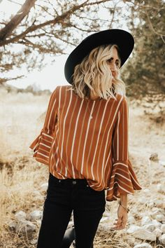 "Orange Blouse Variating Ivory Stripes Round Neckline 3/4 Bell Sleeve Curved Hem Waffle Texture Light + Flowing Fit View Size Chart Model is 5'7"" + Wearing a Small"