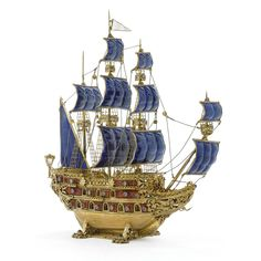 A silver-gilt, enamel, and gem-set nef, probably Hungarian, 20th century modeled as a three-masted galleon, the sides enameled in red with gilt accents, the sails in blue apparently unmarked; in glass display case