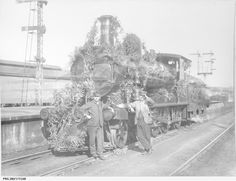 Two train drivers at Adelaide railway station with a locomotive decorated with foliage for Wattle Day