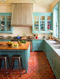 This kitchen pops with the combination of the red tile floor and turquoise cabinet trim. turquoise kitchen by Sawyer | Berson: