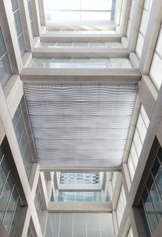 """The 22,500 square meter office building """"Skylab"""" in Geneva was to be equipped with an acoustic ceiling. For this purpose, a new continuous, acoustically effective ceiling solution was developed.  The individual lamellae are joined together by a puzzle connection. Through this new form, no more format restrictions exist for contiguous ceiling panels."""