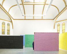 Ugo Rondinone dans son atelier avec quelques spécimens de sa série Walls, des murs de briques colorés, trompe-l'œil minimalistes réalisés sur toile de jute tendue. © Jason Schmidt