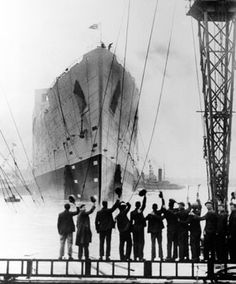 Well-wishers tip their hats to the Queen Mary as she is launched in 1934