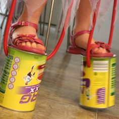 Home-made stilts using tin cans and rope. A fun activity to promote gross motor skills such as balance and coordination. Gross Motor Activities, Movement Activities, Gross Motor Skills, Craft Activities, Toddler Activities, Motor Planning, Kids Moves, Physical Development, Teaching Tools
