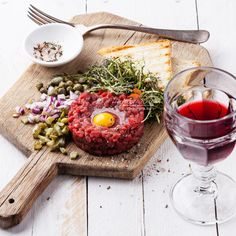 Beef tartare with capers and fresh onion on board with wine. Photograph тартар by Natalia Lisovskaya on 500px