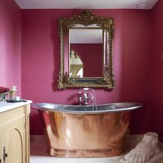 Statement wall colour  Try adding a twist to a traditional bathroom scheme by contrasting boldly coloured walls with equally eye-catching fittings. Here, hot pink provides the perfect foil to a copper roll-top bath and an elegant mirror.