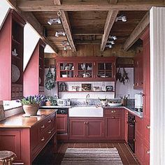 Barn Kitchen.... love the combo of red cabinets and old wood beamed ceiling