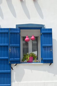 House in Thassos, Greece. White stucco, grey trim, bright blue doors and window shutters, fuscia accents