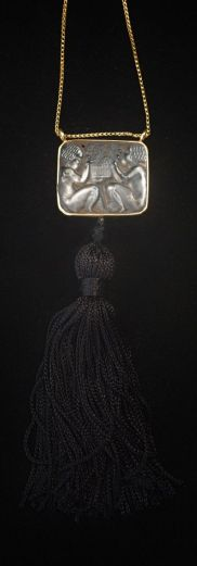 *Rene Lalique, Wingen-sur-Moder. 'Putti' pendant, 1920s. 2.7 x 3 cm. Clear glass, moulded, part matted. Signed: R. Lalique (engraved). Mounting and chain of yellow gold (added). Black tassel.