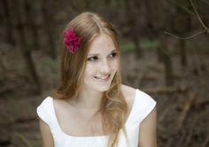 braut mit offenen haaren und pinker blume aus seidenorganza, schlichtes brautkleid mit trägern und überschnittenen schultern, raffung am ausschnitt (Foto: Hanna Witte) (http://www.noni-mode.de)