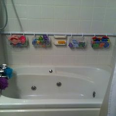 Brilliant!!! I'm so doing this! - Shower Rod against back wall with wire hanging baskets for tub toy storage.