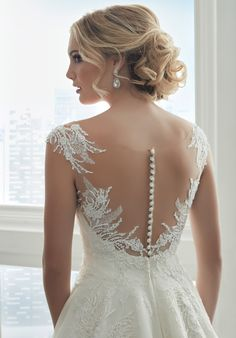 This illusion neckline, A-line gown has been carefully decorated with multiple lace and embroidered appliqués. The bodice is carefully beaded with dainty pearl beads and sequins, while a delicate lace has been placed along the hem. A deep v at the front neckline has been paired with an illusion back. Covered buttons help to open and close the center back. Lace & Tulle - Color Availability: Ivory/Champagne/Nude, Ivory/Ivory/Nude, White/White/Nude