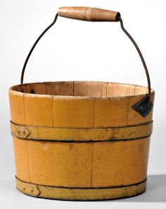 """Skinner's - The Shaker Collection of Erhart Muller, Auction 2898M. June 4, 2016. Lot: 48.  Estimate: $1,000-1,500.  Realized: $2,829.  Description:  Shaker Yellow-painted Pail, Canterbury or Enfield, New Hampshire, 19th century, pine staves and bottom, original paint, diamond-shaped bail plates, iron hoops with ends clipped to a """"V,"""" hardwood convex handle with traces of red stain with scribe line in the center, staves joined with V-shaped tongue-and-groove joints, painted in black on bottom…"""