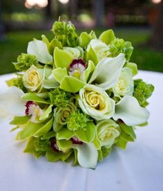 Bridal bouquet of green Roses and Cymbidium Orchids, white miniature Calla Lilies, and Bells of Ireland tips   ---   Photo via Project Wedding