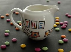 "Milk Jug from the Scrabble collection, with message: ""The Milky Way"" Hand Painted Ceramics by artist Caro Spinette. Photo by Kate Sims."