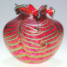 Humler & Nolan Good Daniel Lotton vase created in opaque red and decorated with silvery gold plumes pulled aboutthe surface. THe top of the vase was given special attention by hand shearing the edge formulating a six petal flowerhead. Height and diameter is 5 inches. Circa 1992