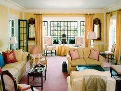 Kristi Nelson's yellow cottage living room features large windows, white molding, and a formal sitting area.