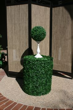 Circular objects covered in faux boxwood mats. Boxwood balls and foam cylinder add some artificial greenery to the event.