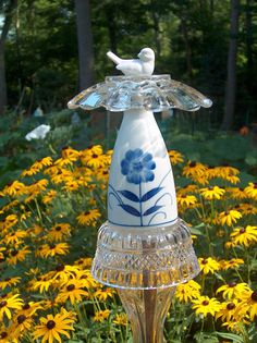 This beautiful glass and ceramic totem will add whimsy to any garden or flower pot. Display high among tall flowers or low to the ground with your border plants. Five separate, reclaimed pieces were creatively attached to make this stunning piece. The blue and white combo will look nice with all colors in the garden. The blue flower is on the front and back of this totem. Height: about 16 Width: about 5 Stake not included. Photos show a 1/2 wide conduit pipe, copper pipe or bamboo s...