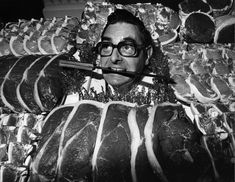 circa 1975: The winner of the Dewhurst's Master Butcher of the Year, James Pegg, poses with a knife between his teeth and a selection of meat. (Photo by Evening Standard/Getty Images)