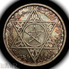 "Another piece from Morocco's Jewish heritage. An official Moroccan currency coin from 1953. Morocco's Pentagram inside the Star of David. The following phrase is inscribed around the coin in Arabic: ""The Mohammadian Sherifian Treasury - Moroccan Kingdom""."