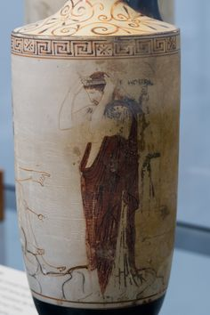 "A deceased woman adorns herself for going to the underworld. To the left, Hermes is waiting for her. Lekythos attributed to the Phiale Painter, a painter active around 460 to 430 BC.   Attic white-ground red figured Lekythos Attributed to ""The Phiale Painter"" ca. 440 – 430 BC Munich. Antikensammlungen."