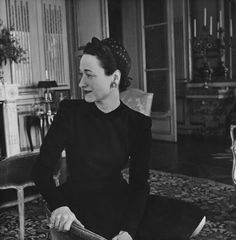 The Duchess of Windsor, sitting in her Paris apartment, and wearing a long-sleeved black dress and a miniature printed silk sailor hat, by Maud et Nano,1946.