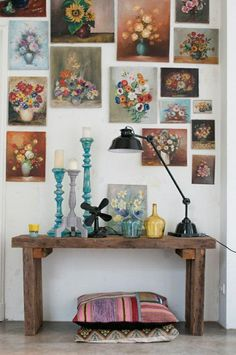 Very pretty and interesting arrangement of flower art around a desk with equally cool stuff on it.