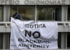 A security guard removed a banner hung from a balcony of the Finance Ministry building in Athens.