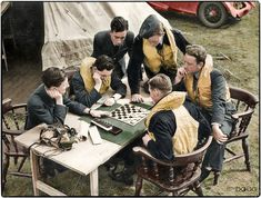 Boulton Paul 'Defiant', British and New Zealand pilots and gunners of No 264 Squadron RAF, pass the time with a game of draughts while waiting at readiness outside their dispersal tent at Kirton-in-Lindsey, Lincolnshire. Summer 1940.