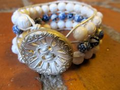 Classical Themed Triple Row Bracelet. White floral designed bead on the outside with white and blue floral beads on the inner row. The button is an antique acquired at Taylor's Button shop in London, England.