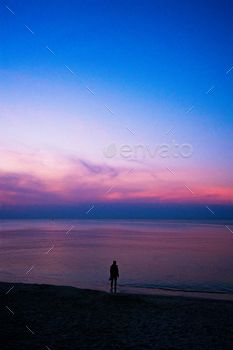 Lonely man walking on the sea beach at sunset